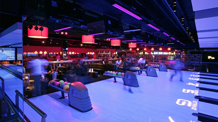 Dark room with neon lights and bowling lanes