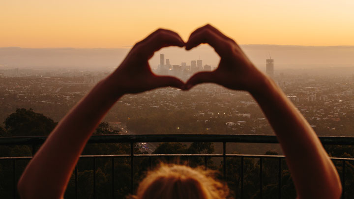 Hands in love heart over Mt Coot-tha sunrise
